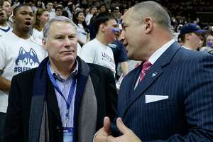 In this Feb. 13, 2017 file photo, American Athletic Conference commissioner Mike Aresco, left, talks with Connecticut athletic director David Benedict, right, before an NCAA college basketball game between UConn and South Carolina in Storrs, Conn.