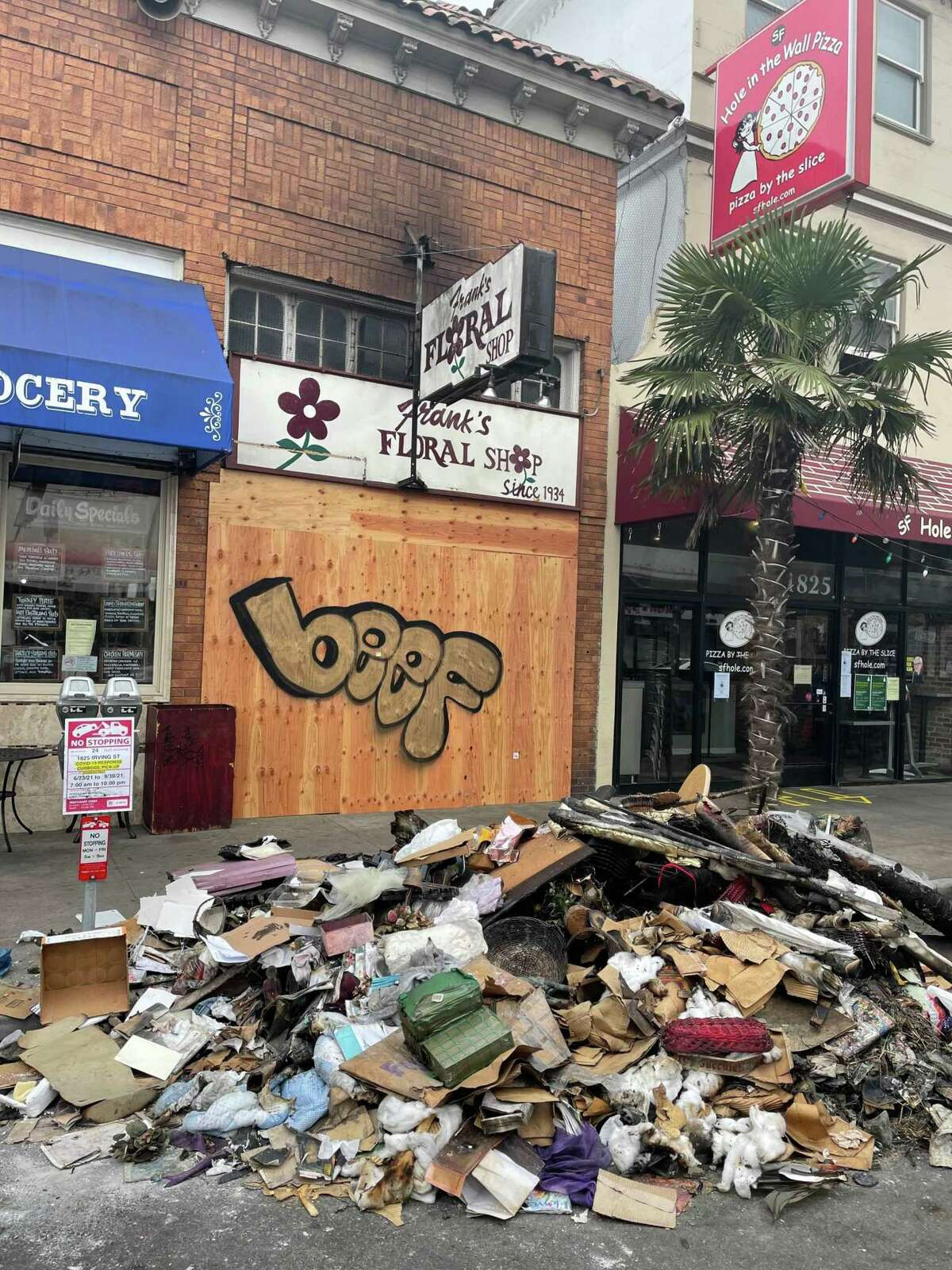 Charred trash is piled outside Frank's Floral Shop in San Francisco after the store was robbed and torched.