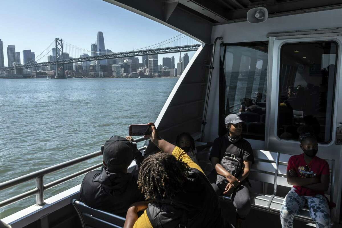 The Henry family of Alameda takes photos of the scenery aboard the San Francisco Bay Ferry as it arrives in San Francisco. At a time when many Bay Area transit operators are struggling to restore service, the Ferry was the first operator to exceed pre-pandemic levels in July and nearly doubled weekend service starting Labor Day weekend.