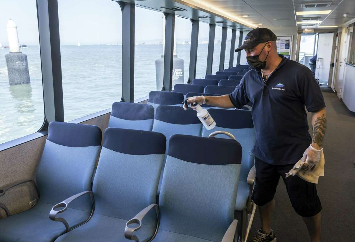 Crew member Tim Torres sprays down seats between trips on the San Francisco Bay Ferry. At a time when many Bay Area transit operators are struggling to restore service, the ferry was the first operator to exceed pre-pandemic levels in July and nearly doubled weekend service starting Labor Day weekend.