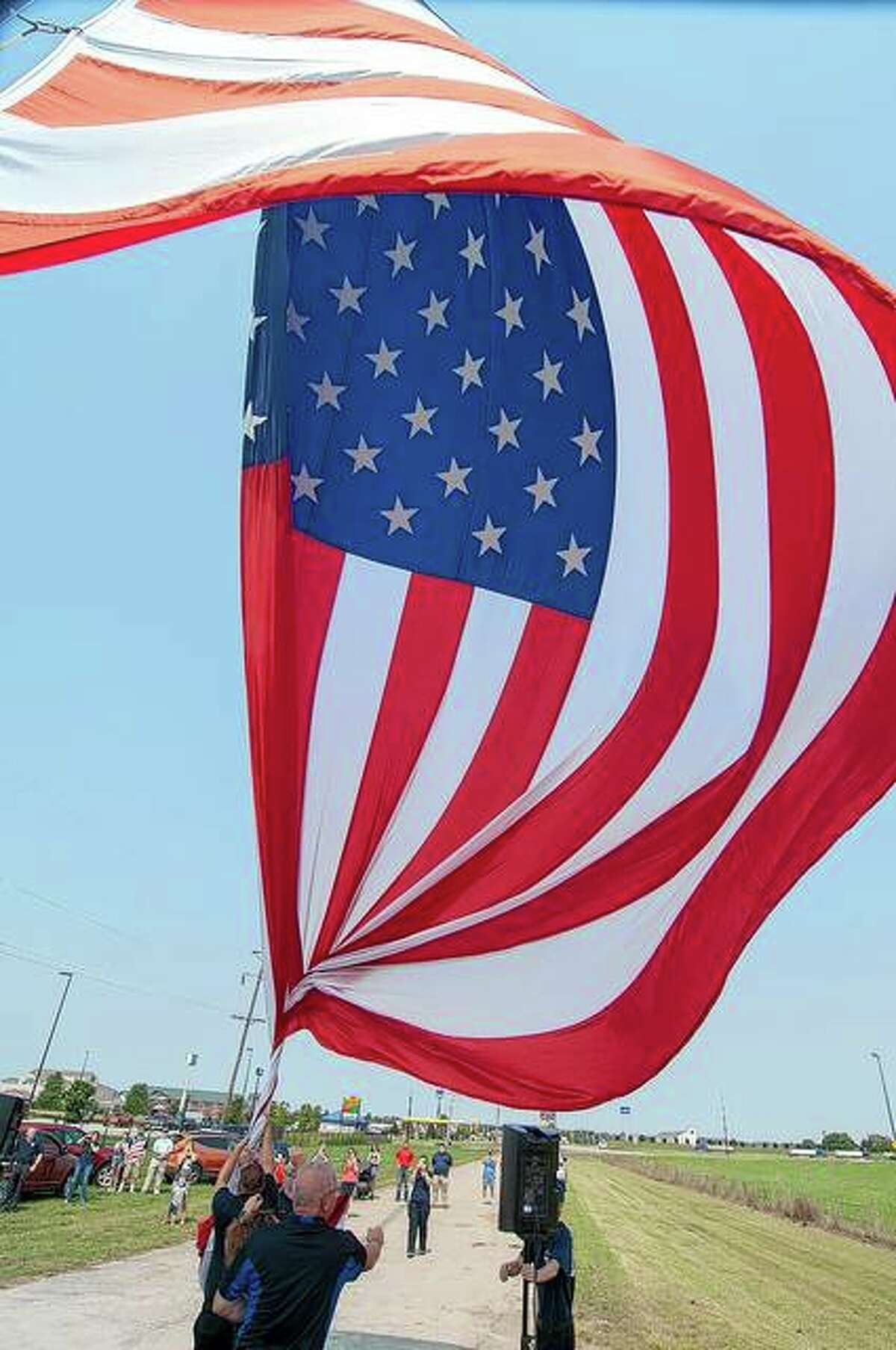 South Jacksonville Fire Department volunteers hold a flag as it is raised Saturday to ensure it doesn't touch the ground. The flag, at South Main Street and Interstate 72, is 30 feet by 50 feet large.