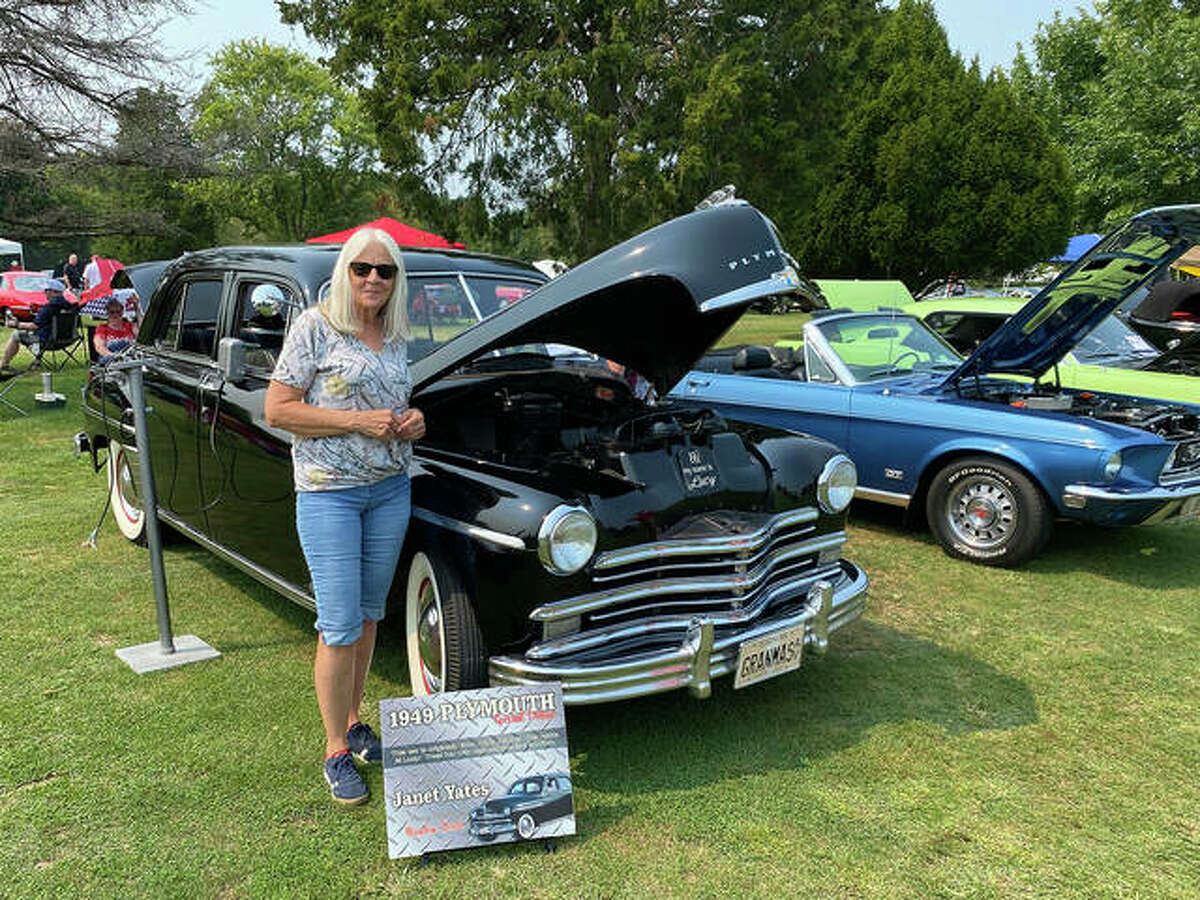 Janet Yates from Edwardsville stands in front of her 1949 Plymouth during the Kicks on 66 car show Saturday. Like many carmakers after World War II, 1949 was the first truly all-new model year for Plymouth. Nineteen forty-six through 1948 models were warmed-over 1942s, which sated most public demand until the all-new models were ready.