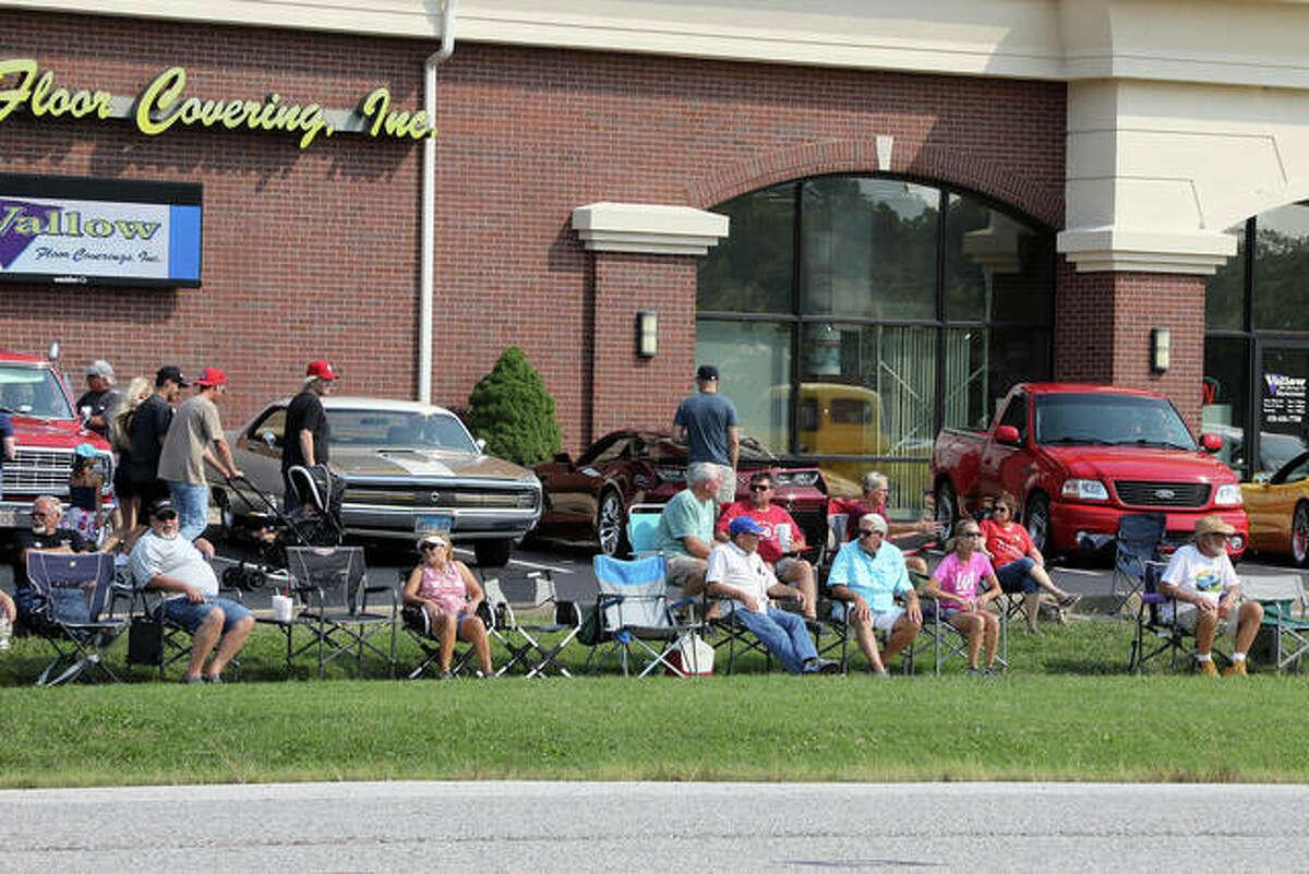"""Interested parties line Route 157 to enjoy the Kicks on Route 66 Ultra Car Show and Cruise Saturday at Vallow Floor Coverings in Edwardsville. Behind them, various muscle cars and music trucks were parked as one of the designated """"pit stops"""" along the two-mile cruise route."""