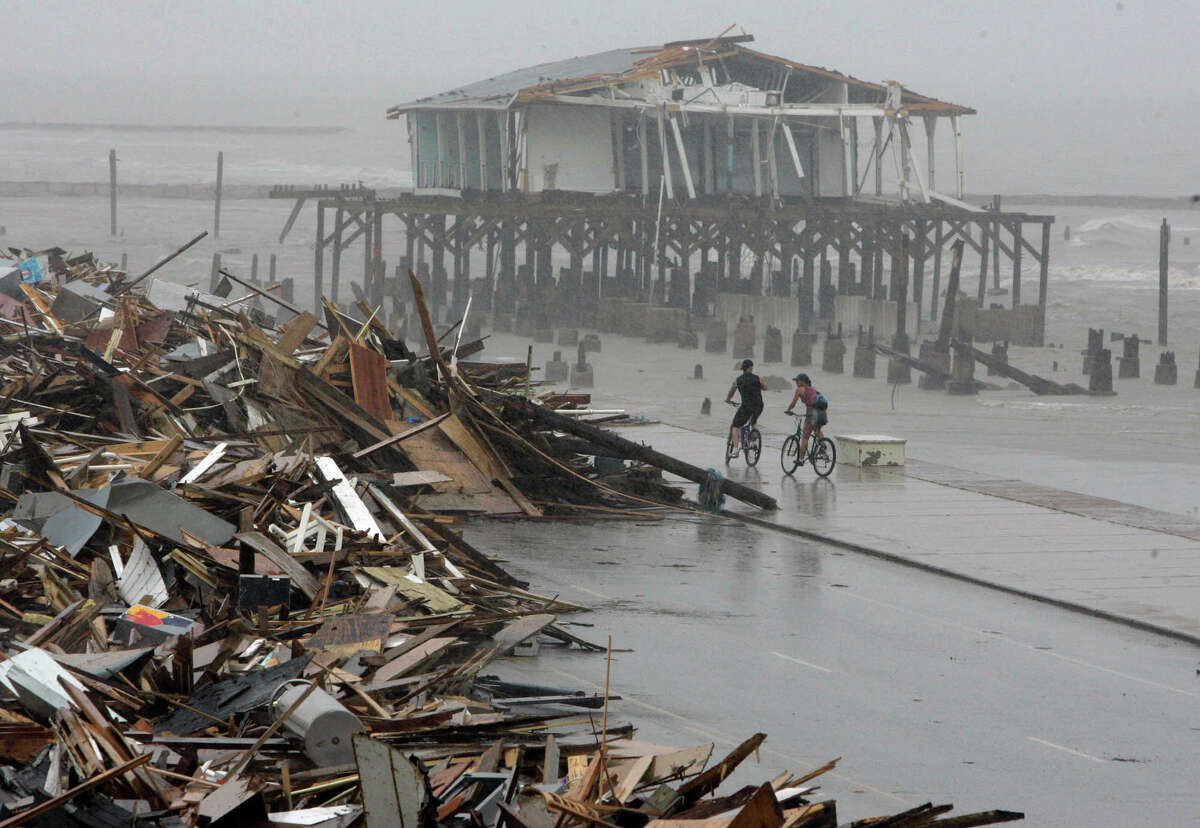 In this Sept. 14, 2008, file photo, cyclists ride past debris piled up on the seawall road after Hurricane Ike hit the Texas coast in Galveston. Most municipal recovery projects in Galveston in the wake of the hurricane have been finished in the eight years since the storm battered the island. Ike made landfall in Galveston on Sept. 13, 2008.