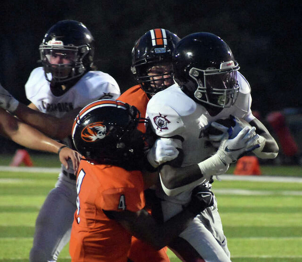 Edwardsville's Kellen Brnfre, left, and Dalton Brown combine to make a tackle in the Champaign Central backfield during the second quarter on Friday inside the District 7 Sports Complex.