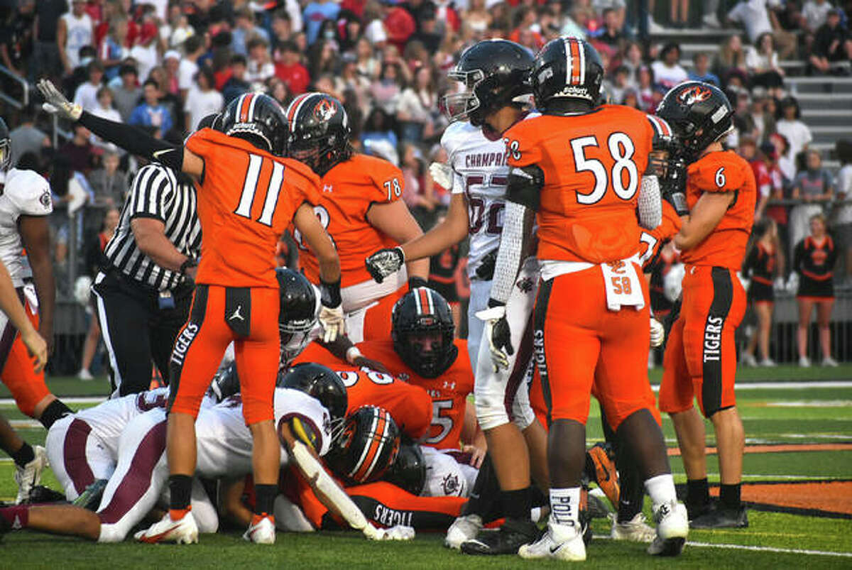 Edwardsville's Makonnen Simmons (No. 11) signals it his team's ball after David Deuanephenh recovered a fumble in the first quarter.