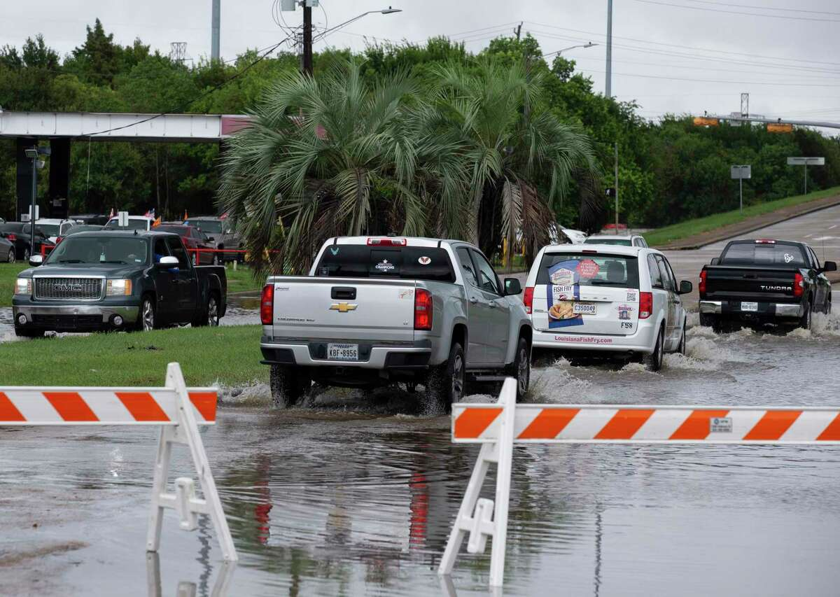 Cars passing road blocks as the flood water from to the rain of Tropical Storm Beta has receded near the intersection of Scarsdale Boulevard and Gulf Freeway Tuesday, Sept. 22, 2020, in Houston.
