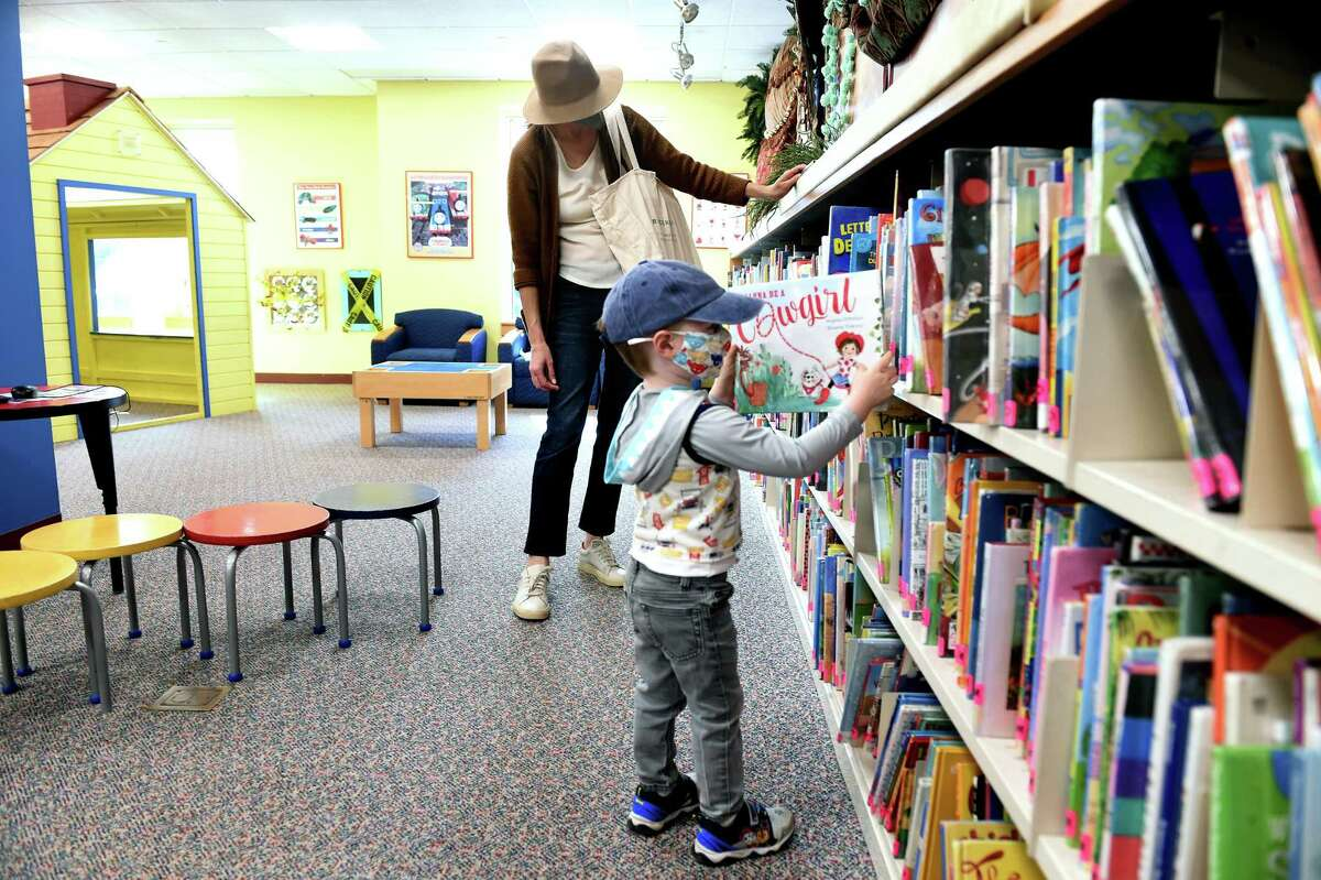A mother and her son browse for books in the children's section of the Guilford Library.