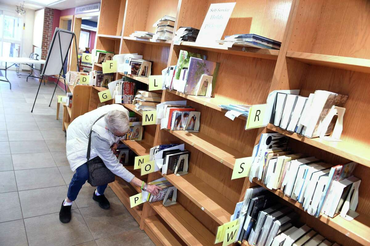 A Guilford resident reaches for a book set aside for her near the entrance of the Guilford Library.