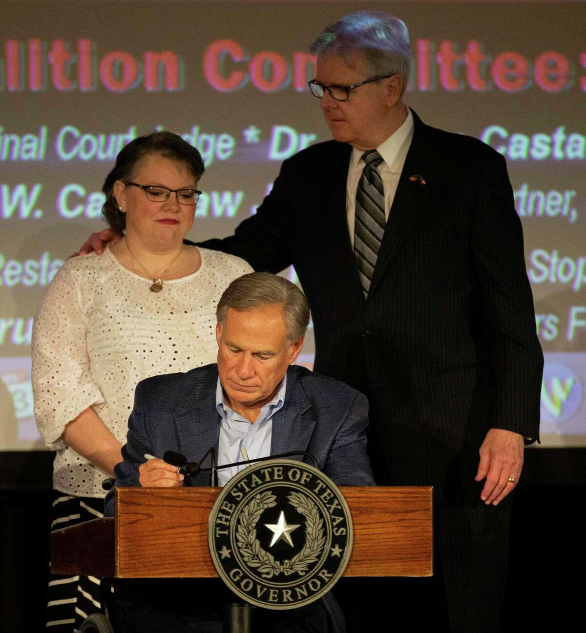 Gov. Greg Abbott signs Senate Bill 6, named the Damon Allen Act in memory of a state trooper who was murdered by an individual out on bond in 2017, into law at the Safer Houston Summit Monday, Sept. 13, 2021, at Bayou Events Center in Houston. Lt. Gov. Dan Patrick, back right, consoles Kasey Allen, widow Allen, in the back.
