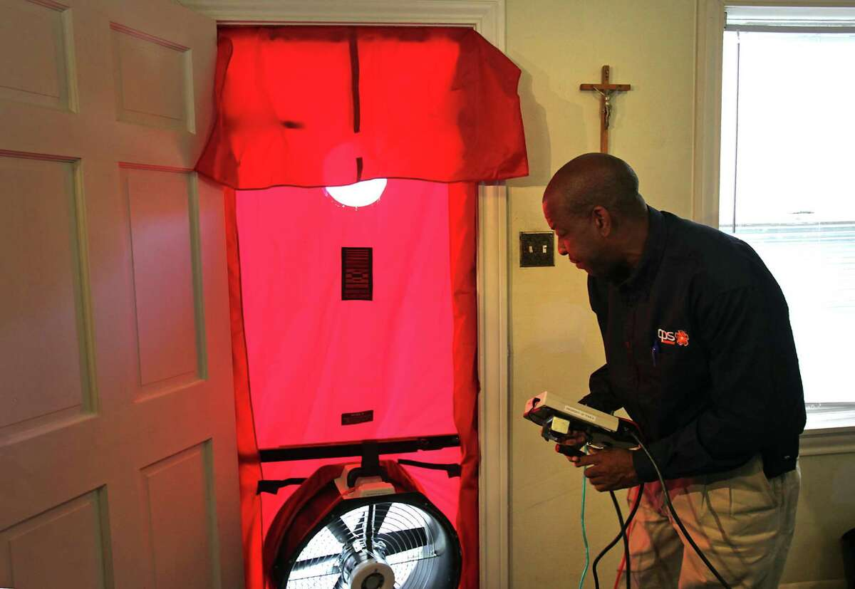 Kirk Nuckols, a field representative for CPS, sets up a blower door to check for air leaks in a customer's home in this 2011 file photo.