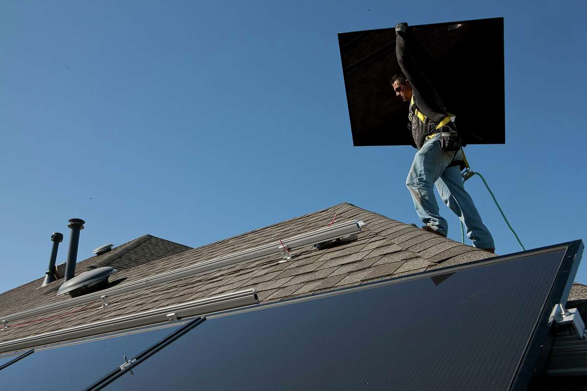 A worker with a solar installation company installs a rooftop system.