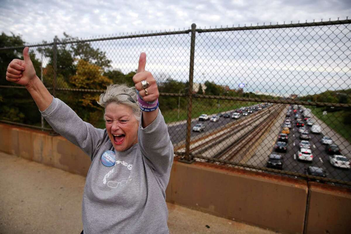 FILE: Veronica Wolski stands on a pedestrian bridge on Chicago's Northwest side while getting her political message out to drivers below on the Kennedy Expressway, Oct. 7, 2016.