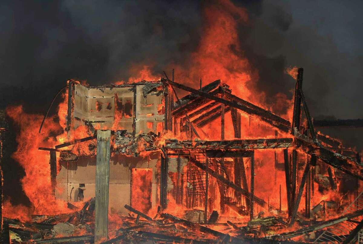 A home burns on Marina Drive above Lake Mendocino during the Hopkins fire, Sunday, Sept. 12, 2021 in Calpella, Calif., in Mendocino County. (Kent Porter/Santa Rosa Press Democrat via AP)