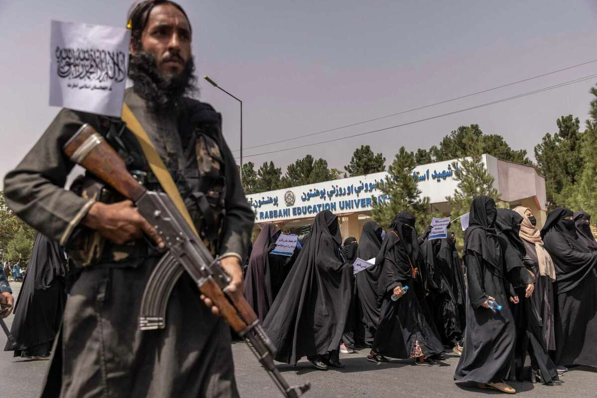 How could 2,500 troops - as President Biden was reportedly advised to keep in Afghanistan - have kept the Taliban at bay in Afghanistan? Here, a Taliban soldier stands guard as women march in support of the new regime in September.