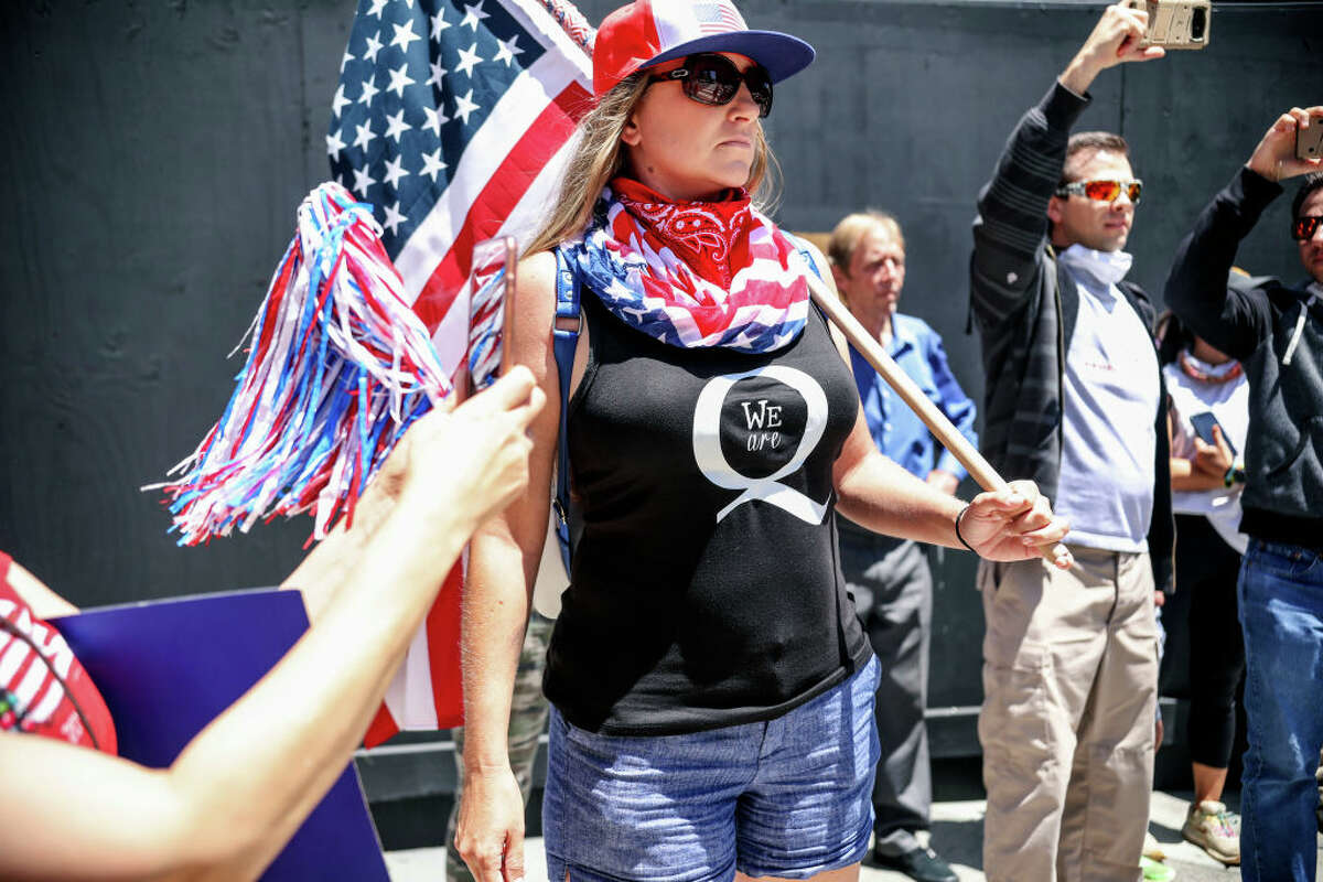 A woman sporting a shirt supportive of QAnon conspiracy theories protests against California's stay-at-home directives on May 1, 2020, in San Diego.