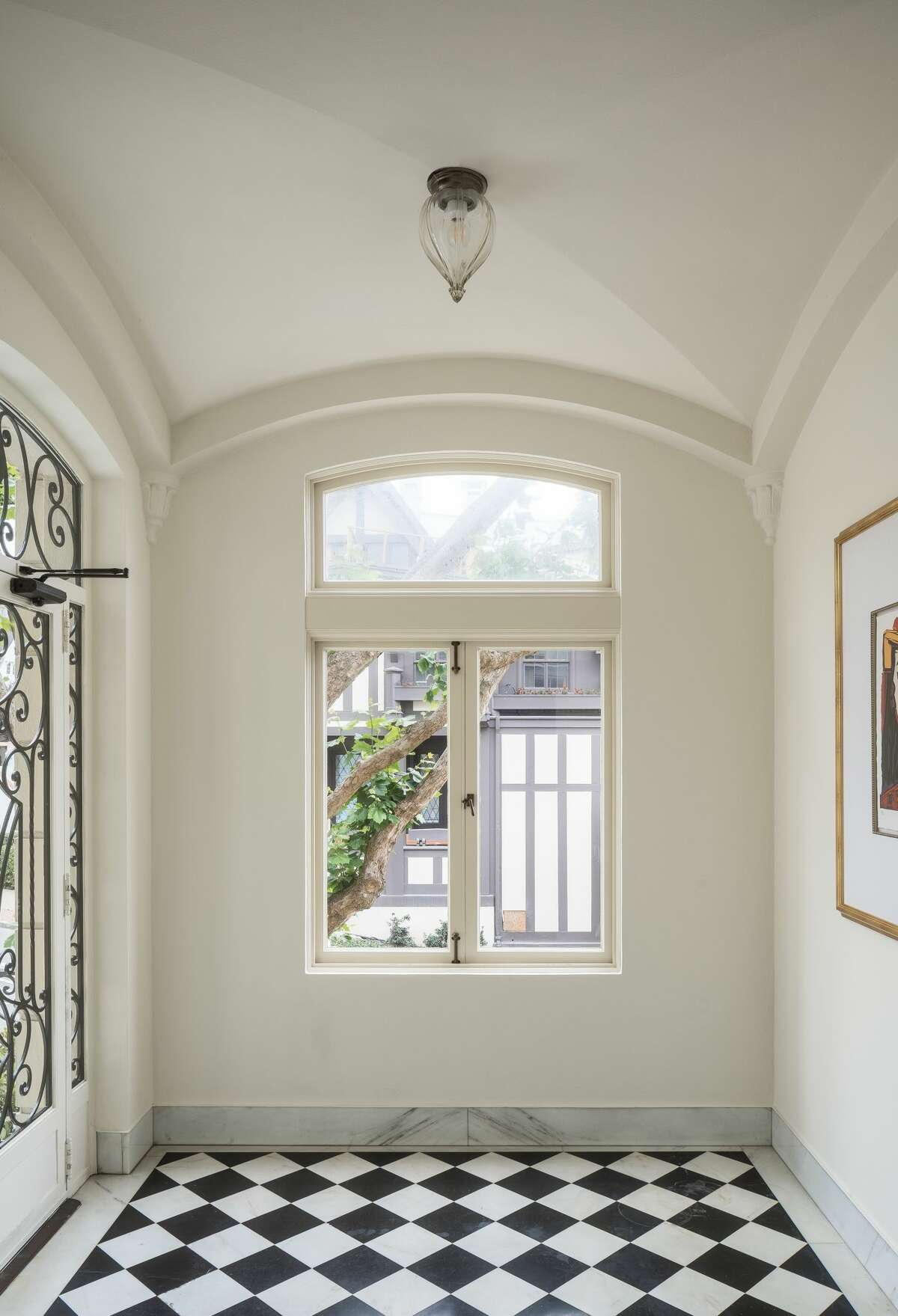 The entry room highlights the iron and glass front door and tiled floor.