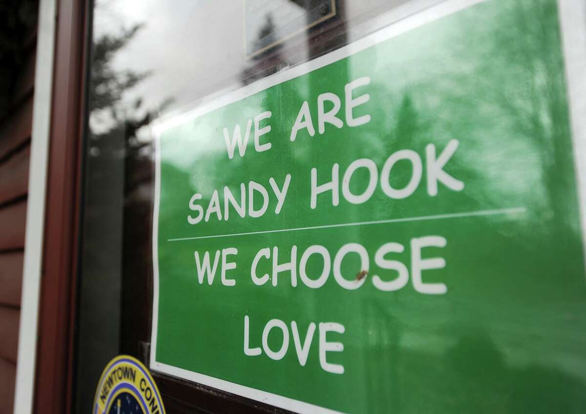 A sign in the window of a Church Hill Road business on the second anniversary of the Sandy Hook Elementary School killings in Newtown, Conn.on Sunday, December 14, 2014.