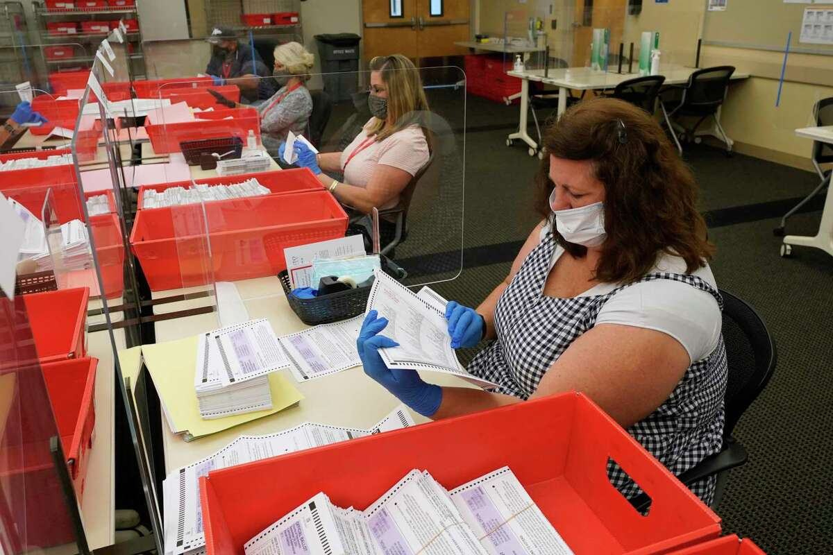 Election workers at the Sacramento County Registrar of Voters office in Sacramento inspect ballots that have been received for the recall election.