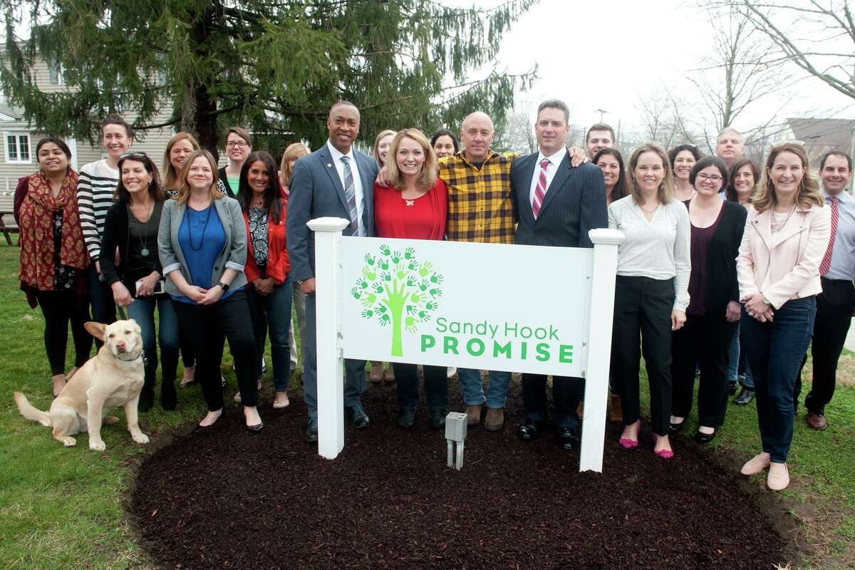 Robert Fuller, right, Assistant Special Agent in Charge of the FBI's New Haven Field Office and Charles Grady, left, an FBI Community Outreach Specialist, stand with Nicole Hockley, Mark Barden and others from Sandy Hook Promise in Newtown. April 8, 2019. Sandy Hook Promise were presented with the FBI Director's Community Leadership Award.