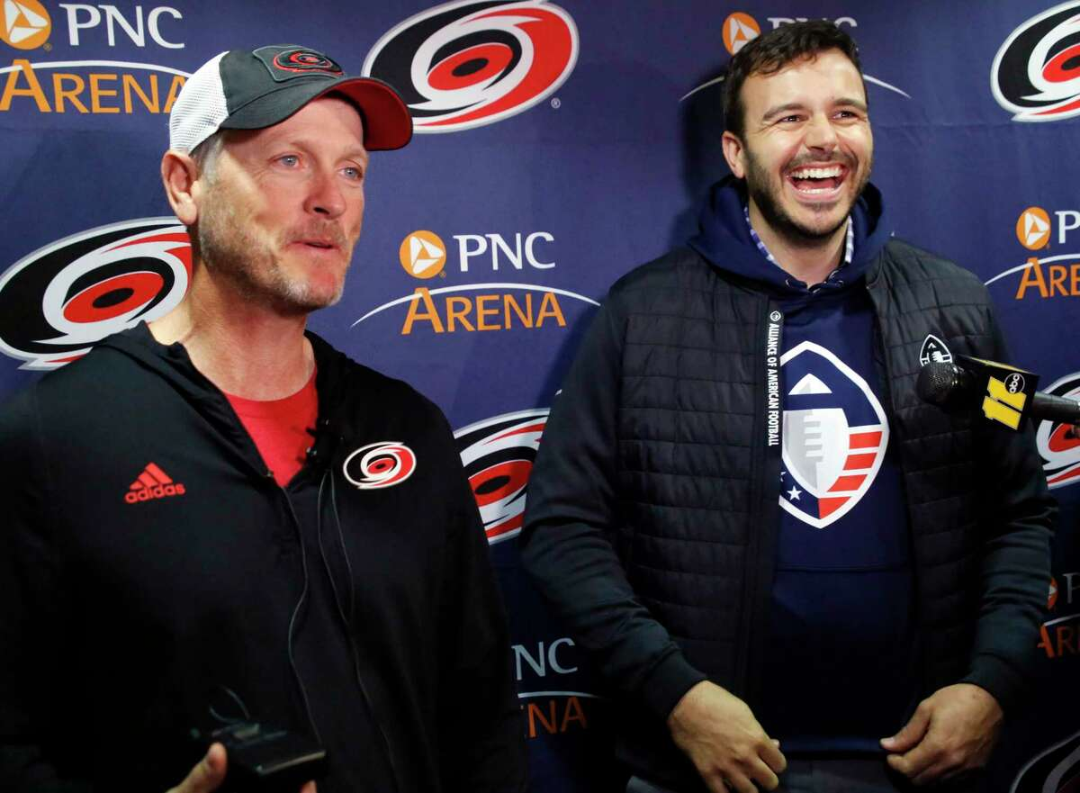 Thomas Dundon, left, majority owner of the Carolina Hurricanes, and Charlie Ebersol, co-founder and CEO of the Alliance of American Football, talk to the media in 2019 in Raleigh, N.C. Dundon and Ebersol are now at odds over the terms of a settlement of a lawsuit brought by AAF players against the now-defunct league and its backers.