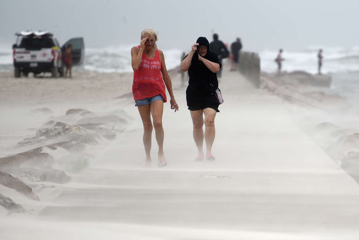 People shield their face from wind and sand ahead of Tropical Storm Nicholas, Monday, Sept. 13, 2021, on the North Packery Channel Jetty in Corpus Christi, Texas. Lifeguards patroled the beach to warn people of the upcoming conditions. (Annie Rice/Corpus Christi Caller-Times via AP)