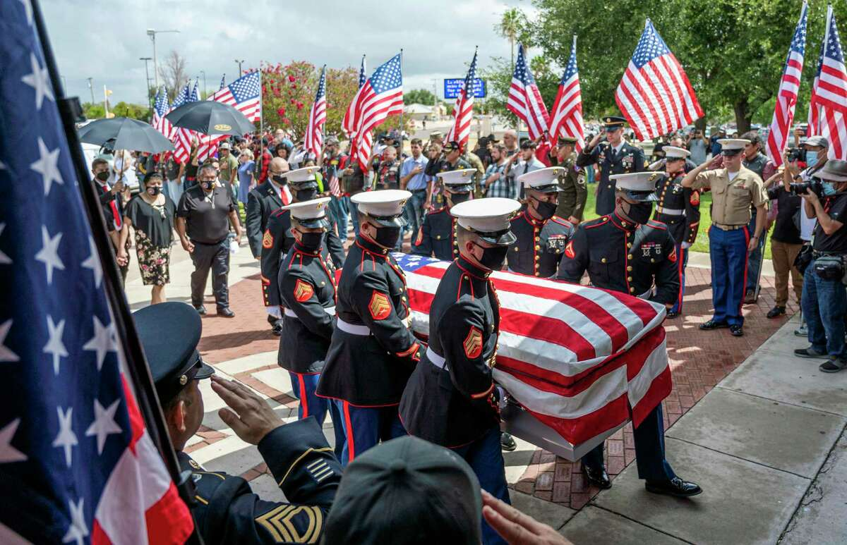 Current and former service members salute Lance Cpl. David Lee Espinoza, Monday, Sept. 13, 2021, as his body is carried into St. Patrick's Church for a mass.