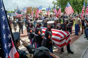 Current and fromer service members salute Lance Corporal David Lee Espinoza, Monday, Sept. 13, 2021, as his body is carried into St. Patrick's Church for a mass.
