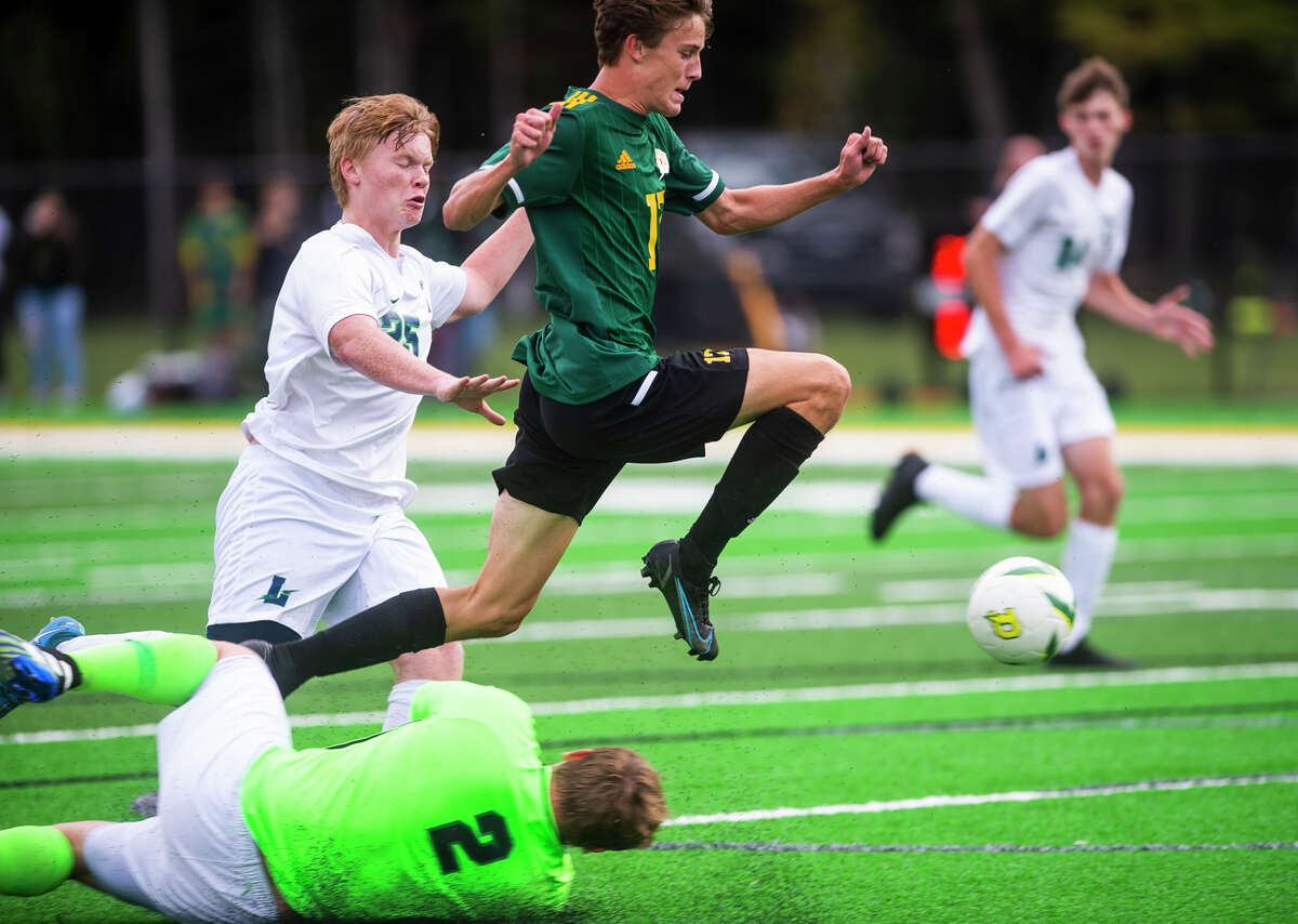 Dow's Isaac Skinner leaps past the opposing goalkeeper in an attempt to score a goal during the Chargers' game against Lapeer Monday, Sept. 13, 2021 at H. H. Dow High School. (Katy Kildee/kkildee@mdn.net)