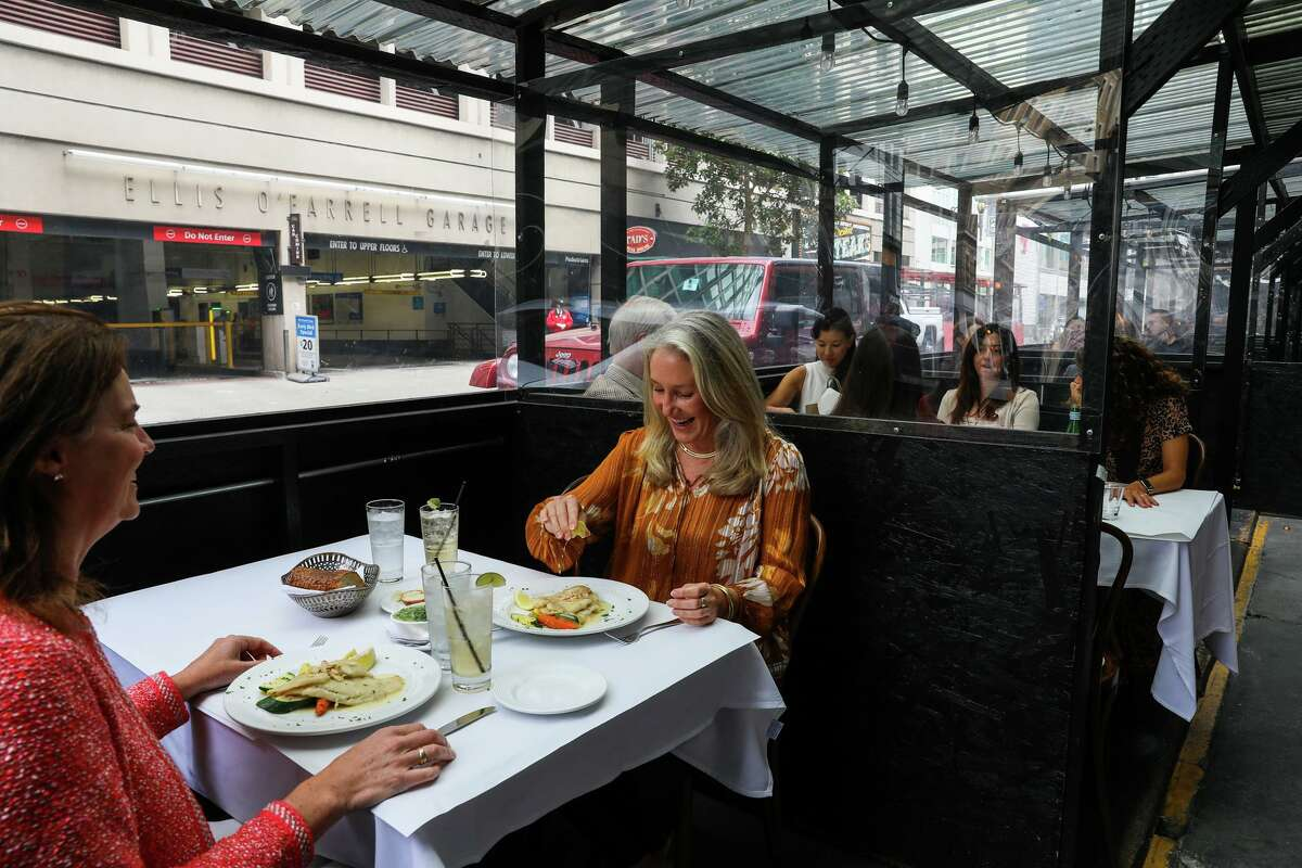 Regulars Karin Flood (left) and Leslie Gay have lunch in the parklet at John's Grill, which has been open in S.F. since 1908.