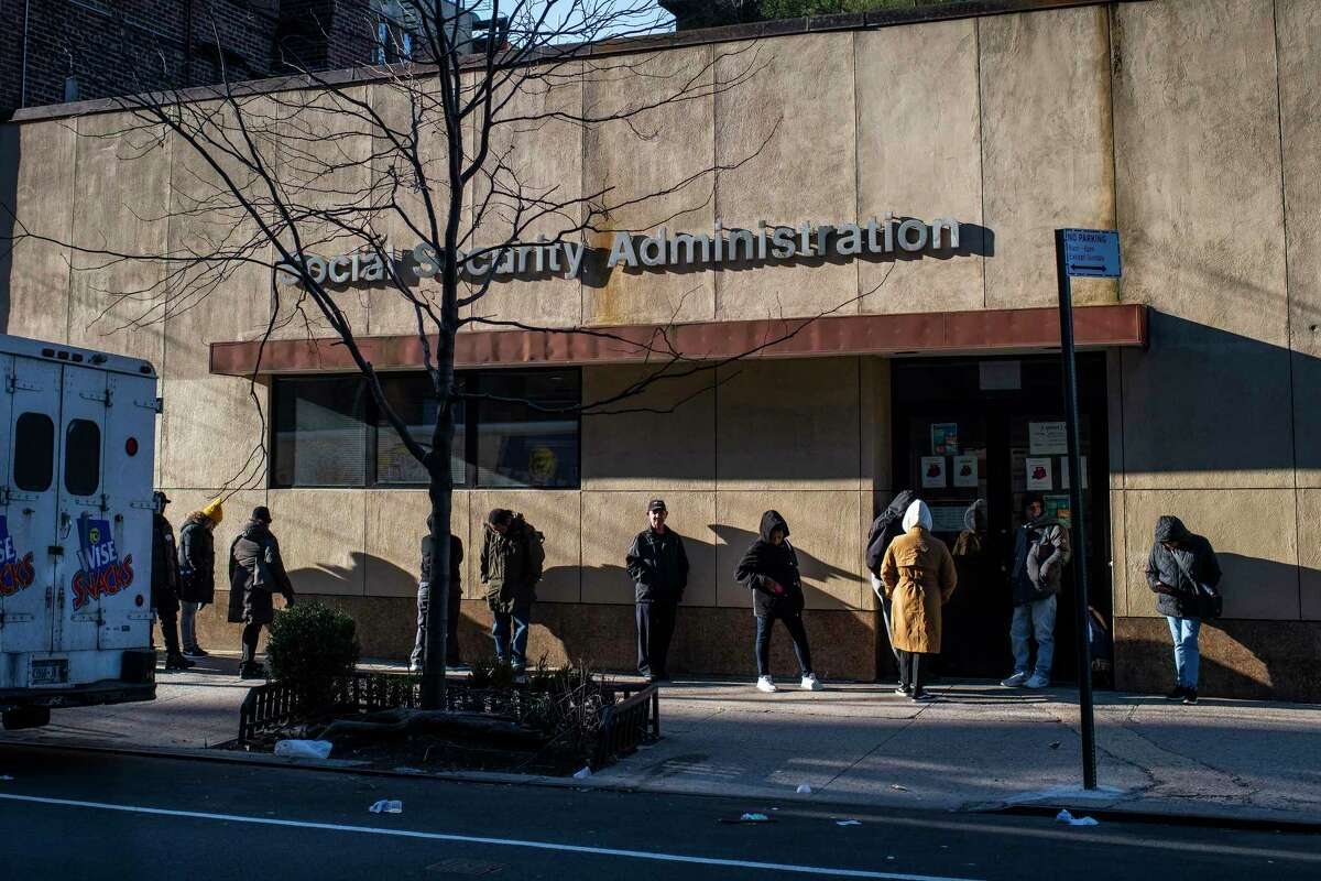 People wait in a carefully spaced line outside a Social Security Administration office. Annual government reports on the solvency of the programs underscored the questions about the long-term viability of Social Security and Medicare.