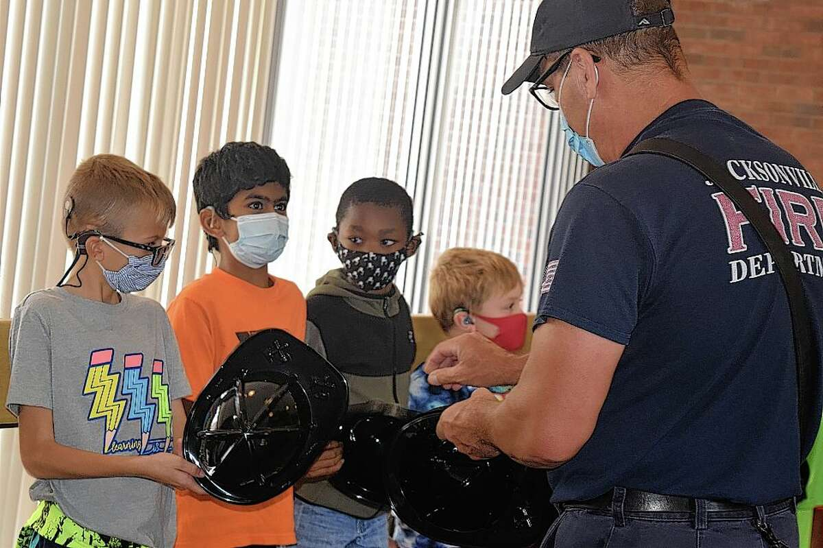 Jacksonville firefighter Jim Williams hands out helmets Monday to students at the Illinois School for the Deaf after they completed the challenge of climbing 11 flights of stairs in honor of firefighters and other emergency responders who died at the World Trade Center during the Sept. 11, 2001, attacks.