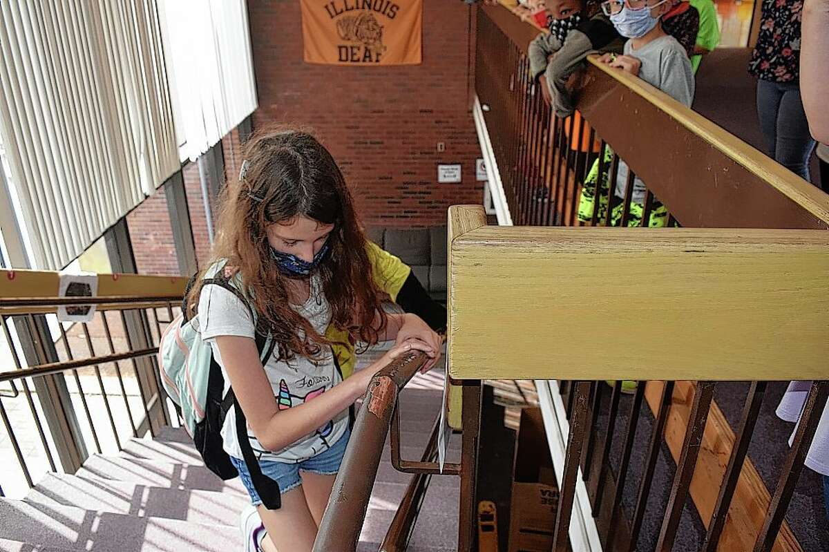 Illinois School for the Deaf fourth-grader Bailey Roddick runs up the steps in her school Monday to help honor those who died during the Sept. 11, 2001, terrorist attacks at the World Trade Center. Stu
