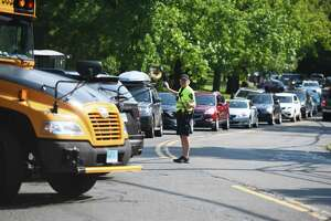 A police officer directs traffic as buses pick up students during dismissal at Brien McMahon High School in Norwalk, Conn. Monday, Sept. 13, 2021. Since students returned to school, traffic at arrival and dismissal has caused significant backups in the area.