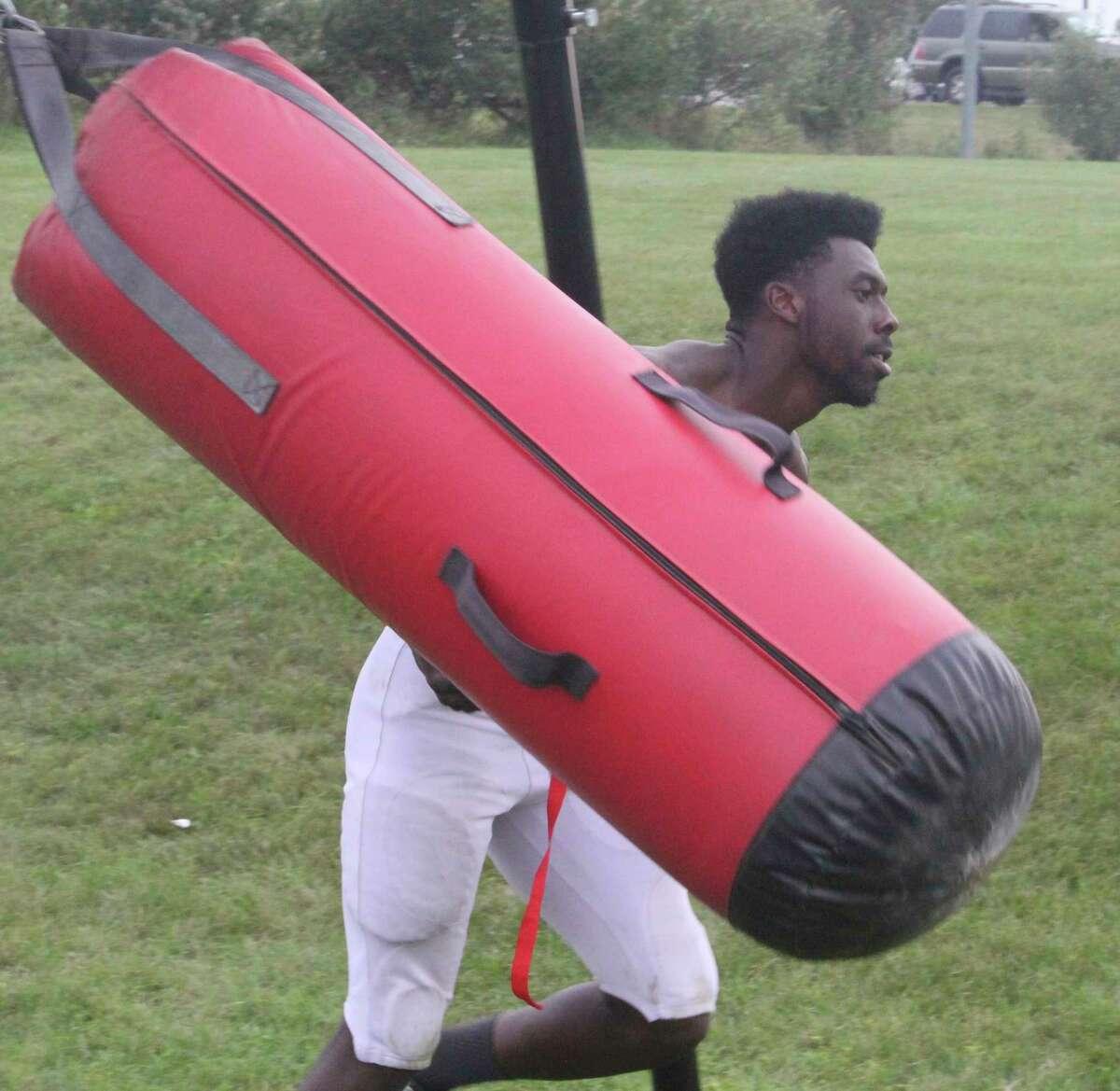 Big Rapids' Jamal Strickland works with the blocking bag after a recent Cardinal practice. (Pioneer photo/John Raffel)