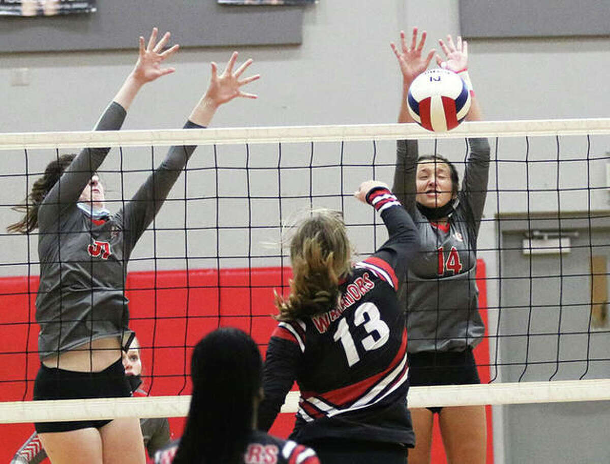 Alton's Grace Carter (right) scores off a block of the attack from Granite City's Emily Sykes (13) while the Redbirds' Reese Plont (left) also goes above the net during a third-place match Saturday at the Alton Invite.