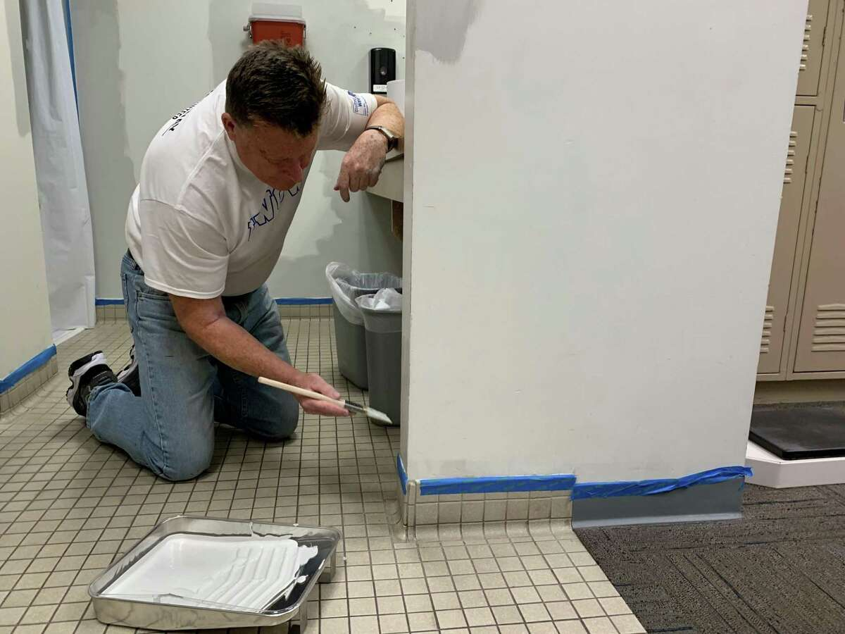 Mark Crook, a Thomaston Savings Bank employee, paints the wall of the men's lockeroom at the Cheshire YMCA. Crook was there with other employees, who were volunteer with the United Way of Greater Waterbury.