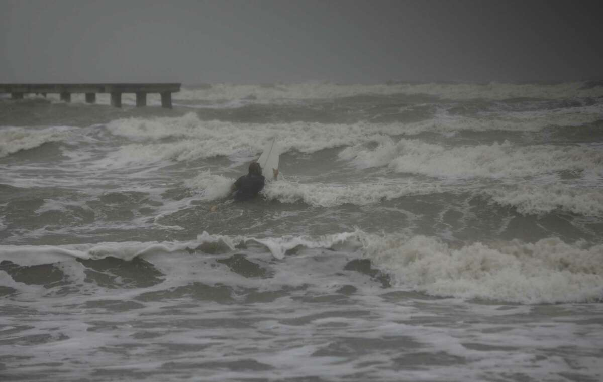 A surfer tries to paddle through the surf as wind and rain from Tropical Storm Nicholas batters the area Monday, Sept. 13, 2021, along the seawall in Galveston.