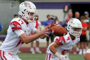 Greenwich quarterback Jack Wilson, left, receives the snap during Saturday's game against Westhill.