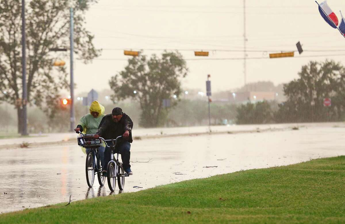 Cyclist make their way down the street in Bay City, Texas as Tropical Storm Nicholas approaches on Monday, Sept. 13, 2021.