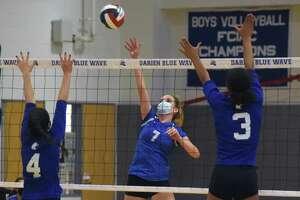 Darien's Jillian Roche (7) sends a shot over the net as Newtown's Lauren Young (4) and Keyera Smith (3) defend during a girls volleyball match in Darien on Monday, Sept. 13, 2021.