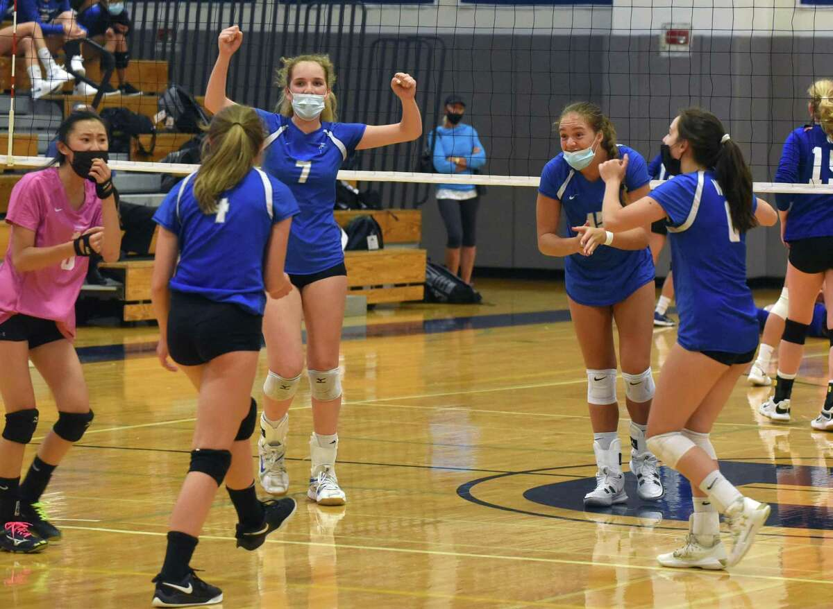 The Darien Blue Wave celebrates a point against Newtown during a girls volleyball match in Darien on Monday, Sept. 13, 2021.