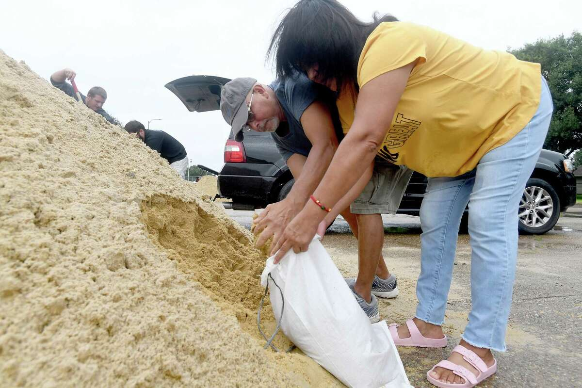 Lily and Israel Rizo fill sandbags just after a site was opened in Doornbos Park in Nederland Monday morning. With Tropical Storm Nicholas expected to make landfall later in the day before tracking east, residents across the area prepared for possible flood impacts. Photo made Monday, September 13, 2021 Kim Brent/The Enterprise