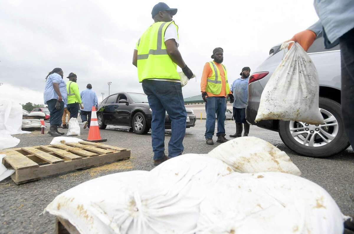 Workers with the City of Beaumont load sandbags into trunks and truckbeds Monday at the Beaumont Athletic Complex. With Tropical Storm Nicholas expected to make landfall later in the day before tracking east, residents across the area prepared for possible flood impacts. Photo made Monday, September 13, 2021 Kim Brent/The Enterprise
