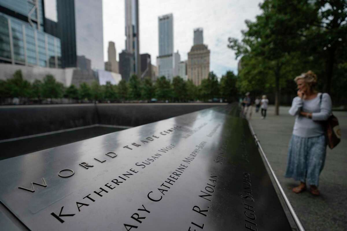 Monique Nagelkerke looks over the north reflecting pool at the 9/11 Memorial & Museum, Monday, Aug. 16, 2021, in New York. (AP Photo/John Minchillo)