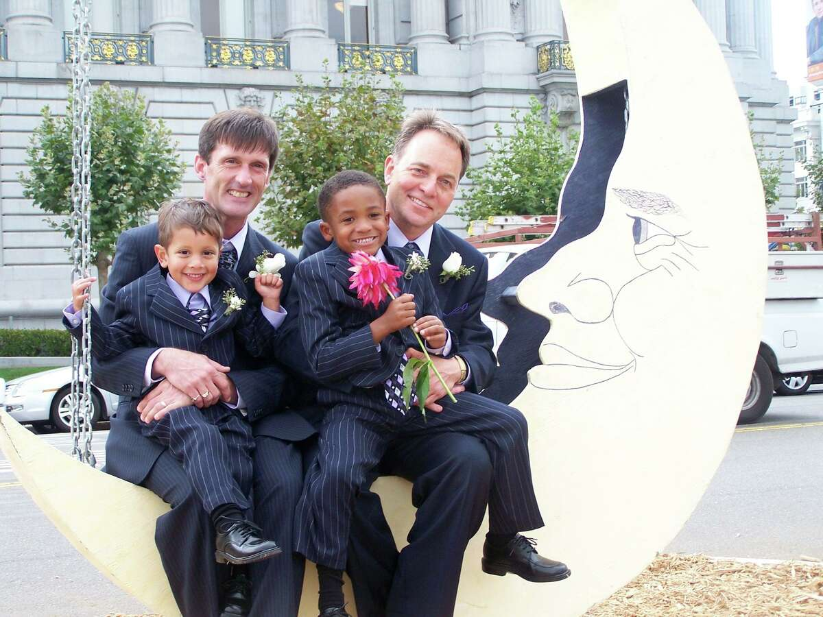 Kevin Fisher-Paulson (back right) with husband, Brian Fisher, on their wedding day in 2008 with adopted sons, Zane (right) and Aidan.