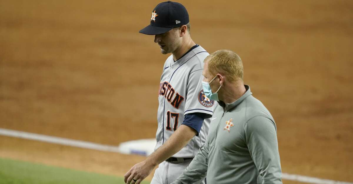 Houston Astros starting pitcher Jake Odorizzi (17) walks off the field with a member of the staff after suffering an unknown injury in the second inning of a baseball game against the Texas Rangers in Arlington, Texas, Monday, Sept. 13, 2021. (AP Photo/Tony Gutierrez)