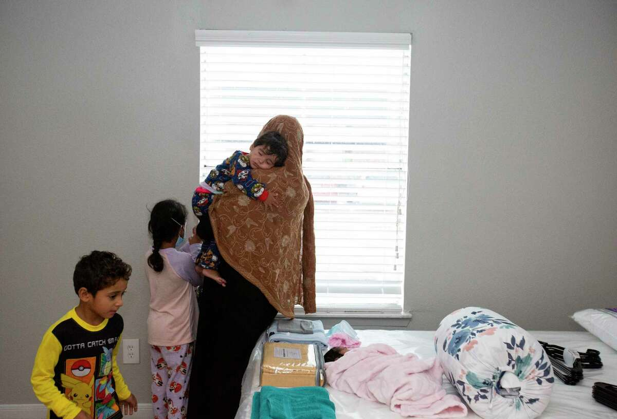 Safia, 32, holds her sleepy 3-year-old daughter, Taqwa, while looking out the window in their two-bedroom apartment, provided by Interfaith Ministries for Greater Houston, after staying at a hotel overnight Monday, Sept. 13, 2021, in Southwest Houston. The Afghan family of seven arrived Houston at midnight with their 5-day-old baby girl, Ajwa, born in the United States.