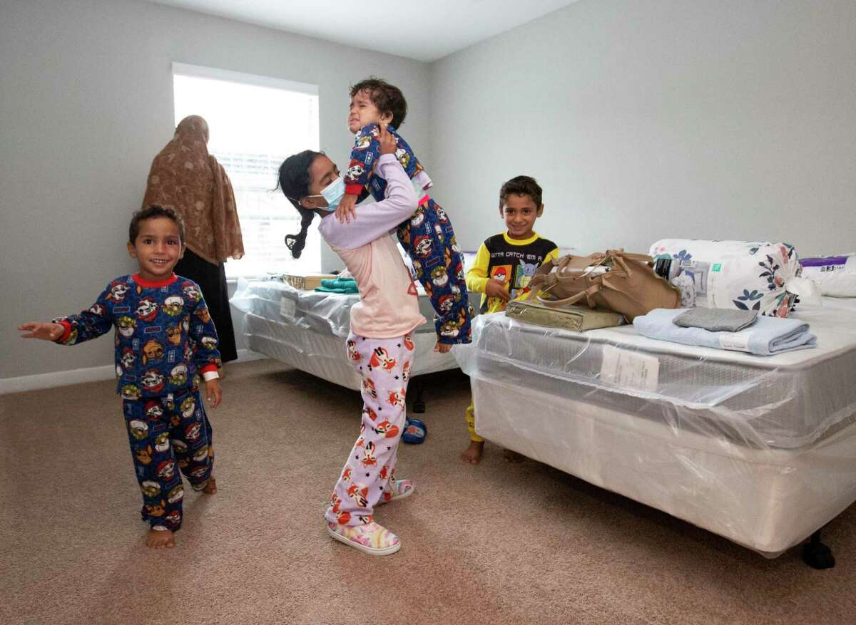 Iqra, 7, picks up her tired sister, Taqwa, while her family is settling in at their two- bedroom apartment, provided by Interfaith Ministries for Greater Houston, after staying at a hotel overnight Monday, Sept. 13, 2021, in Southwest Houston.