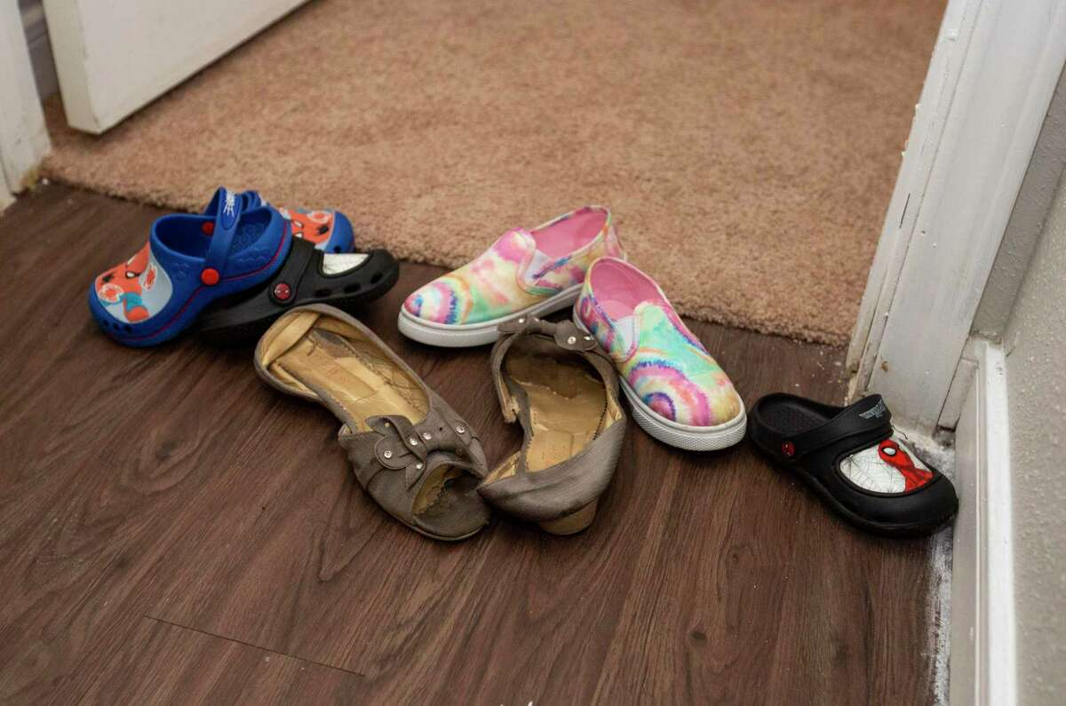 Everyone of the Afghan family leaves their shoes outside a carpeted bedroom as they are settling in a two-bedroom apartment, provided by Interfaith Ministries for Greater Houston, after staying at a hotel overnight Monday, Sept. 13, 2021, in Southwest Houston. The Afghan family of seven is among the first families of parolees arriving after being processed in third countries and on military bases.